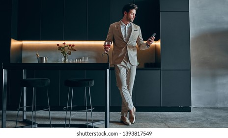 Handsome stylish man in beige suit at home. Standing in modern black kitchen with smart phone in hand and glass of whiskey.