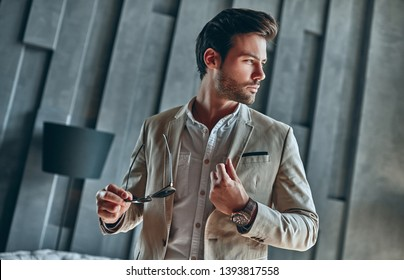 Handsome stylish man in beige suit at home standing with sunglasses in hand.