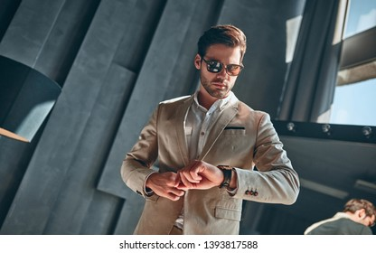 Handsome stylish man in beige suit at home checking time.