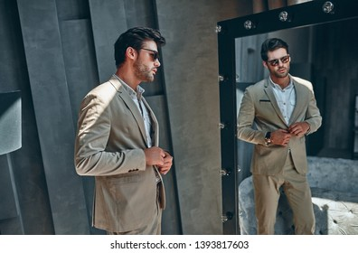 Handsome stylish man in beige suit at home looking at mirror.