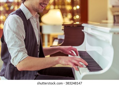 Handsome stylish man in classical vest smiling while playing a piano in a musical shop, cropped