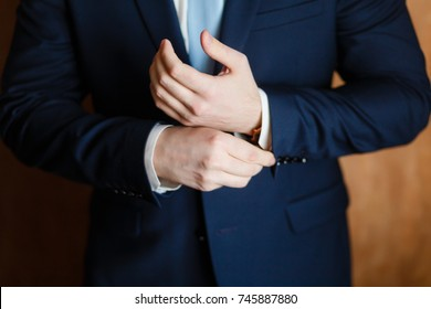 Handsome stylish man dressed in modern formal clothes buttoning jacket. Close up of hands of guy in blue jacket, white shirt. Person ready for wedding celebration, graduation or business meeting.
