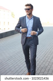 handsome stylish man in elegant suit and sunglasses in the street.