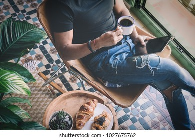 Handsome stylish man in headphones listening to music on electronic tablet and drinking cup of coffee at home. Casual relaxing and rest time concept. Blurred background