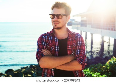 Handsome stylish man in hipster plaid shirt and sunglasses posing near sea side at sunshine, enjoying beautiful view and relax near ocean.