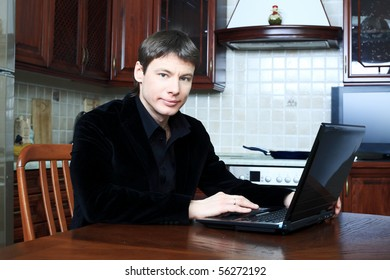 Handsome stylish man at home with a laptop