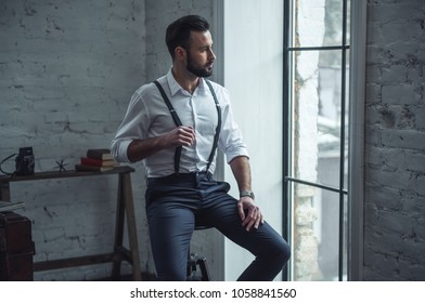Handsome stylish man in suit is holding his suspenders and looking out the window while sitting on chair indoors