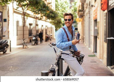Handsome stylish man texting on the phone and driving a bike in the city.