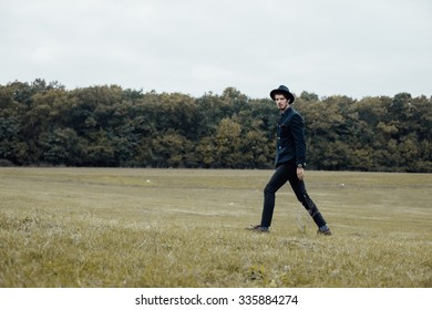 handsome stylish man walking on a green field with cool clothes