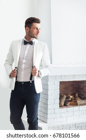 Handsome stylish man in white elegant suit standing near fireplace