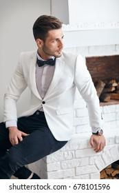 Handsome stylish man in white elegant suit sitting near fireplace