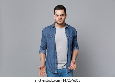 Handsome stylish unshaven young man in denim jeans shirt posing isolated on grey wall background studio portrait. People sincere emotions lifestyle concept. Mock up copy space. Looking camera sceptic