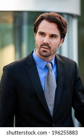 Handsome stylish young businessman standing waiting for someone outside his office building leaning forwards expectantly as he looks to the left of the frame
