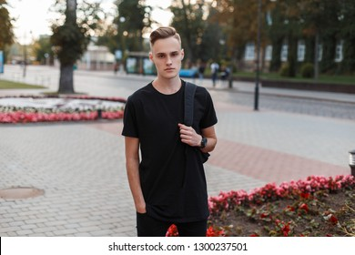 Handsome stylish young man in a fashionable black T-shirt with a stylish backpack with a stylish hairstyle in jeans travels around the city on a warm summer day. Charming stylish guy.