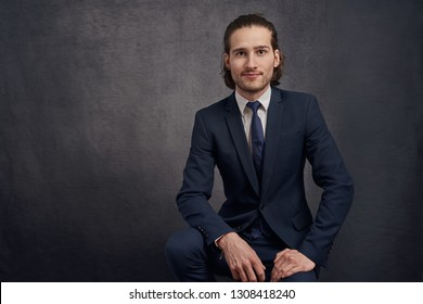 Handsome and stylish young man with long hair, wearing fashionable suit, sitting on bar stool against dark background and looking at camera with calm face.