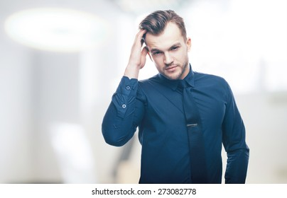 Handsome stylish young man in shirt looking at the camera. Office worker. Business decisions. Beautiful light background