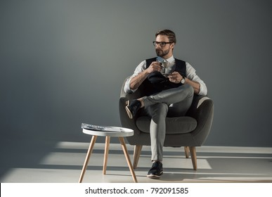 handsome stylish young man sitting in armchair and looking away while drinking coffee
