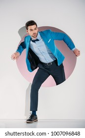 handsome stylish young man in suit and bow tie looking away while stepping through hole on grey