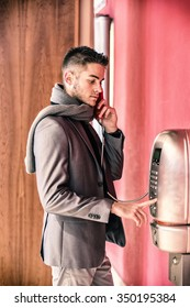 Handsome stylish young man in a tailored jacket and scarf standing using a pay phone waiting for a connection, profile view