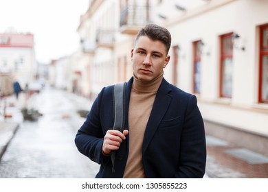 Handsome stylish young man in trendy clothes with a black stylish backpack walks through the city streets on a warm spring day. Successful attractive businessman travels.