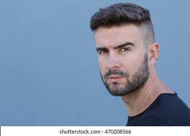 Handsome stylish young man with undercut hairstyle, beard and piercings with copy space