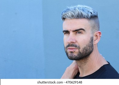 Handsome stylish young man with undercut dyed or artificially colored hairstyle, beard and piercings daydreaming looking away with copy space