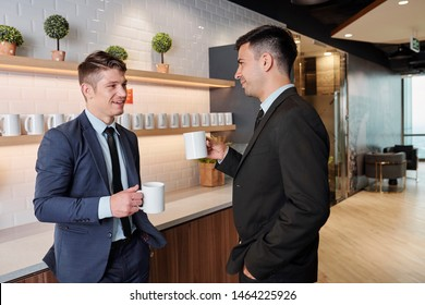 Handsome successful business people driking coffee and talking in office kitchen