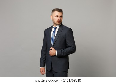Handsome successful confident young business man in classic black suit shirt posing isolated on grey wall background, studio portrait. Achievement career wealth business concept. Mock up copy space