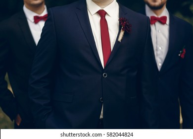 Handsome, successful groom posing with bestmen outdoors, group shot of newlywed groom standing in park with groomsmen in stylish suits
