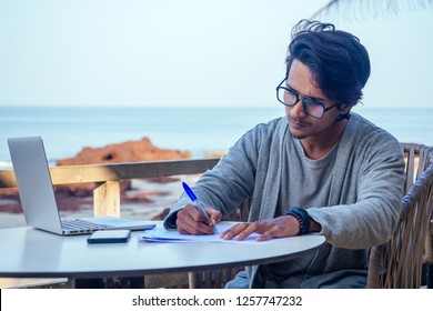 handsome and successful indian man in a stylish well-dressed freelancer working with a laptop on the beach.freelance and remote work.businessman student in a summer cafe on the shore of india ocean