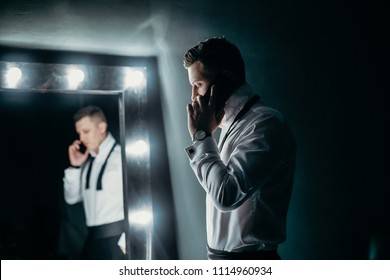 handsome successful man in a white shirt is standing near the dressing mirror and talking on his mobile phone in dark room