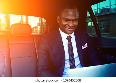 Handsome successful rich african american business men entrepreneur in a stylish black suit and tie sitting in a luxury car and works with laptop. concept of luck and currency market stock exchange