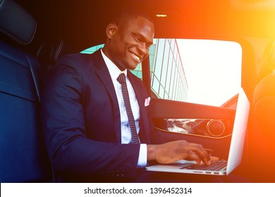 Handsome successful rich african american business men chief in a stylish black suit and tie sitting in a luxury car and works with laptop. concept of luck and currency market