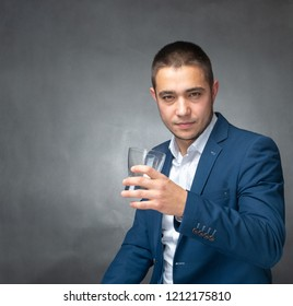 Handsome successfull  businessman in blue suit sitting and showing expressions