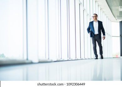 handsome and sucessful senior business man walking in modern office