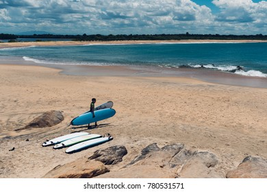 Handsome surfer go to the blue ocean with surfboard in Shrilanka
