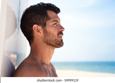 Handsome surfer looking at the sea with his board behind him. Side view