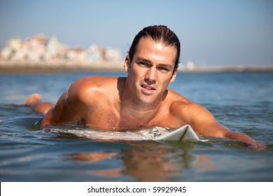 Handsome surfer on his board paddling towards camera