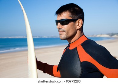 Handsome surfer wearing sunglasses and a wetsuit holding his surf board overlooking the ocean.