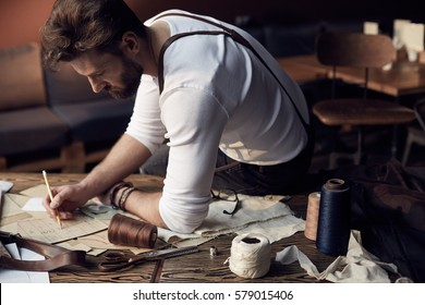 Handsome tailor male with beard in white shirt with brown leather suspenders working near wooden table with threads in amazing atelier with antique furniture and mannequin on background