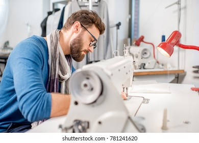 Handsome tailor sewing fabric with a sewing machine at the studio