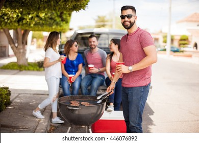 Handsome tall Hispanic man grilling hamburgers and drinking beer outdoors with some friends