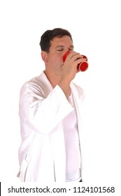 A handsome tall man standing in a white bathrobe and drinking from 