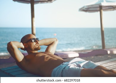 Handsome Tanned Male at the Beach. Holiday And Relaxation Concept