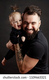 Handsome tattooed adult father holding cute little baby with funny hairstyle close to the body, closing his eyes from tenderness and love.