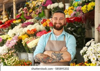 Handsome tattooed florist in flower shop