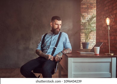 Handsome tattooed hipster in a shirt and suspenders sitting at the desk with a computer, looking out the window in an office with loft interior.