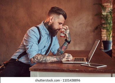 3523b4a7a Handsome tattooed hipster in a shirt and suspenders sitting at the desk,  working on a