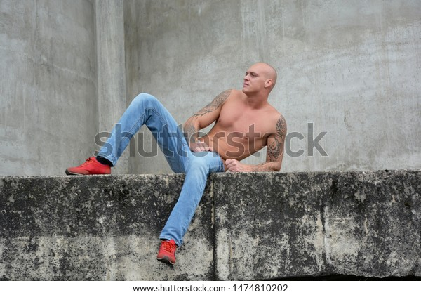 Handsome tattooed male model lying outdoor on wall and looking forward