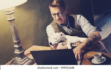 Handsome tattooed man in eyeglasses working at home on laptop while sitting at the wooden table with cute dog sleeping on his hands.Adult guy using modern computer for surfing web